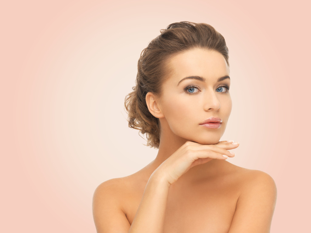 beauty, people and health concept - beautiful young woman touching her face over pink background